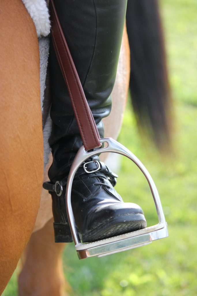 Close up of a rider's tall boot in the stirrup.