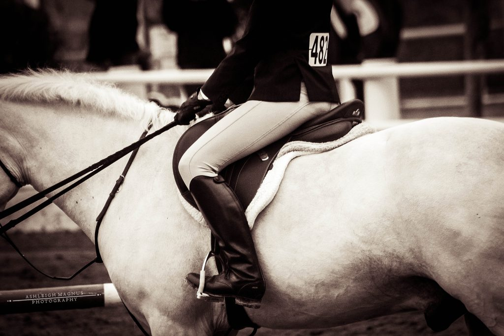 Black and white image of an English rider dressed in show attire riding a horse.