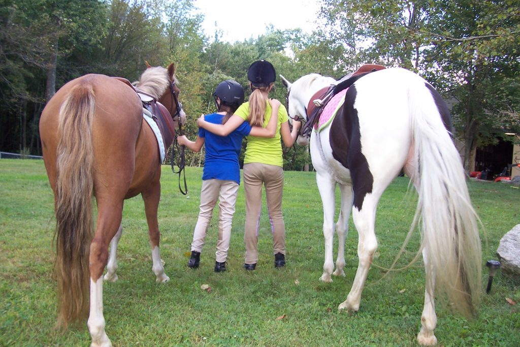 Two young riders at summer camp with arms around each other standing next to a chestnut pony and a black and white paint pony.