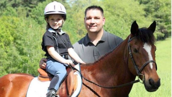 Dad standing next to young daughter on bay pony for Father's Day ride.