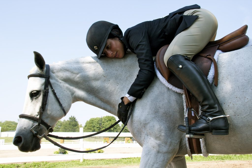 English rider in the saddle leaning down to hug her grey horse's neck.