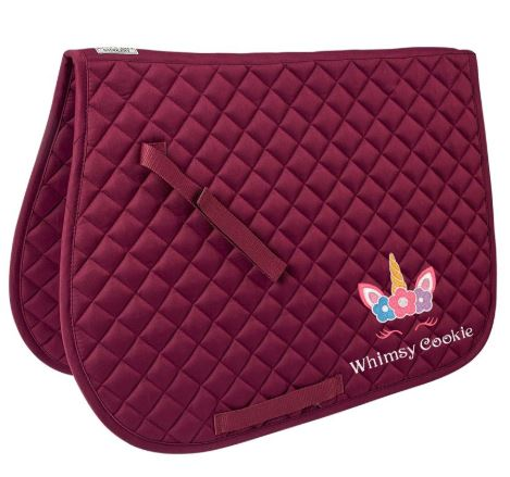 "Burgundy colored quilted saddle pad with colorful unicorn monogram in lower right corner above the monogrammed name, ""Whimsy Cookie."""