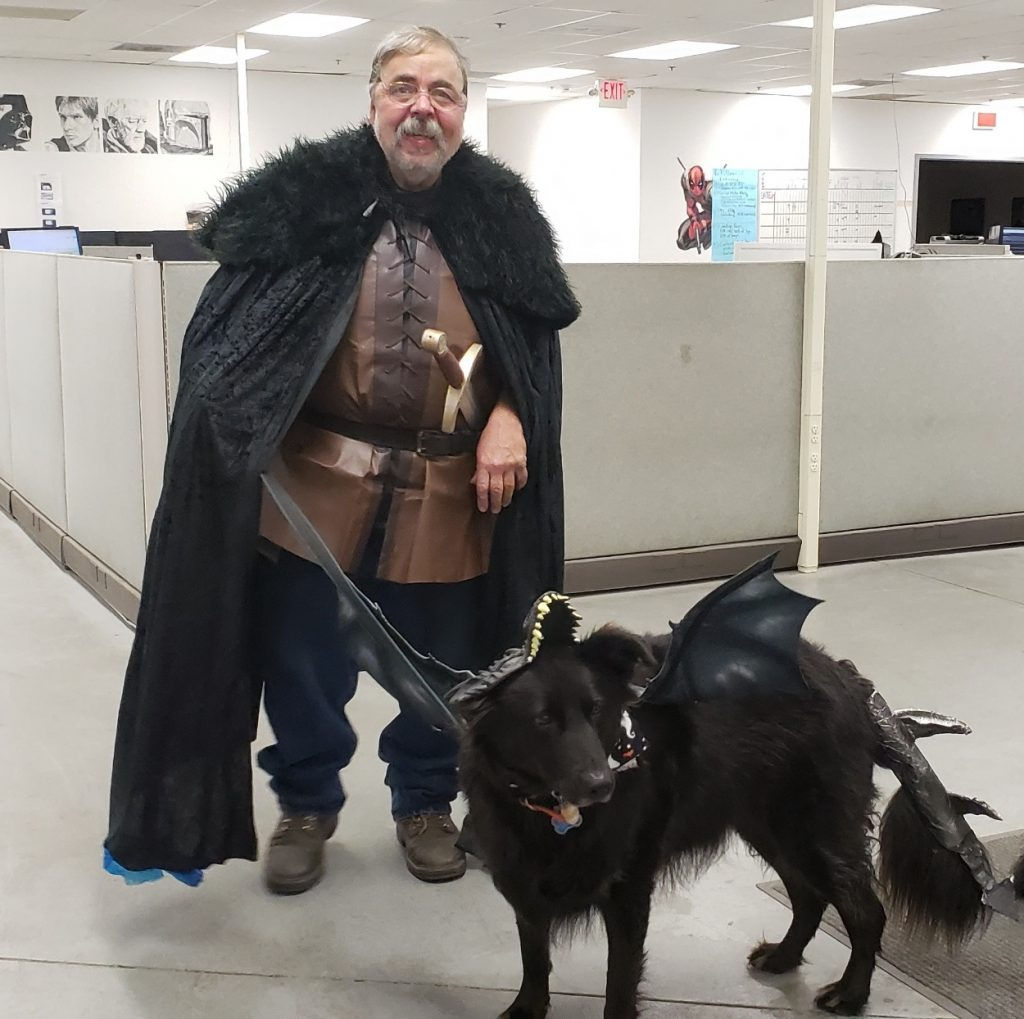 Black dog dressed as a Game of Thrones dragon accompanied by a man dressed in a Jon Snow Halloween costume.