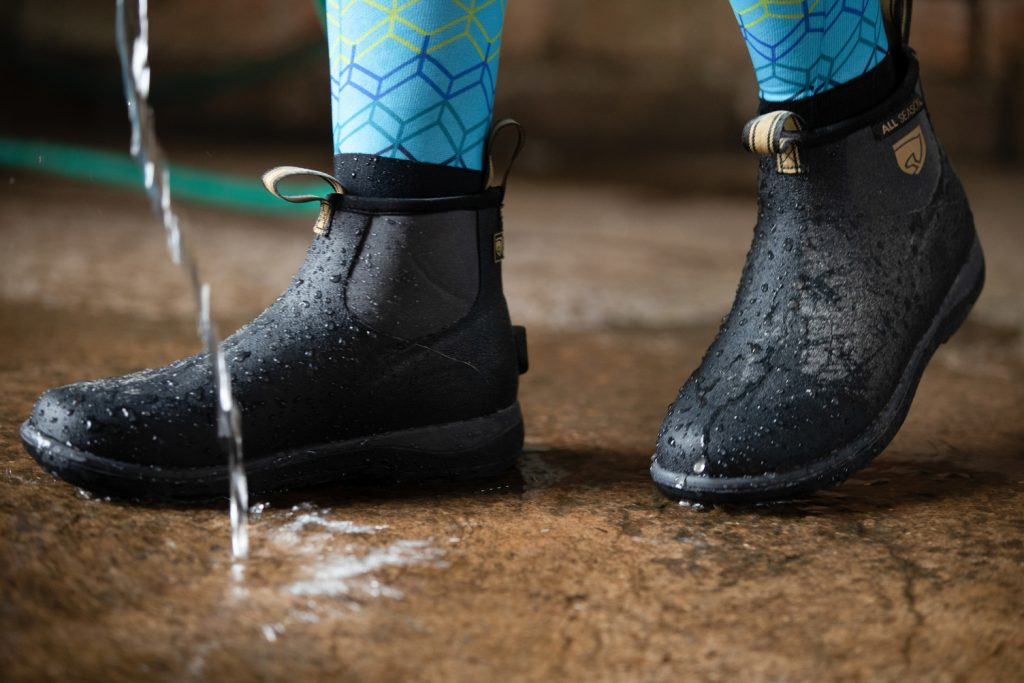 Noble Equestrian Perfect Fit All Season Low Boots in black being worn while hose water is running.