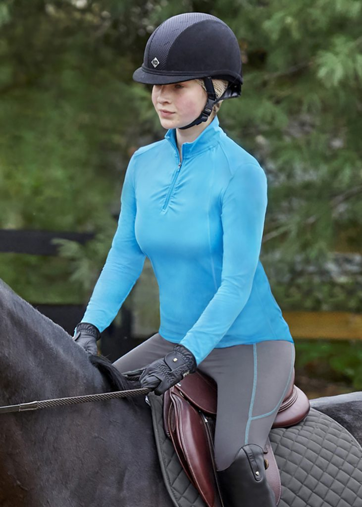 Female rider wearing charcoal and blue jewel colored Stride by Dover Saddlery Tech Tights.