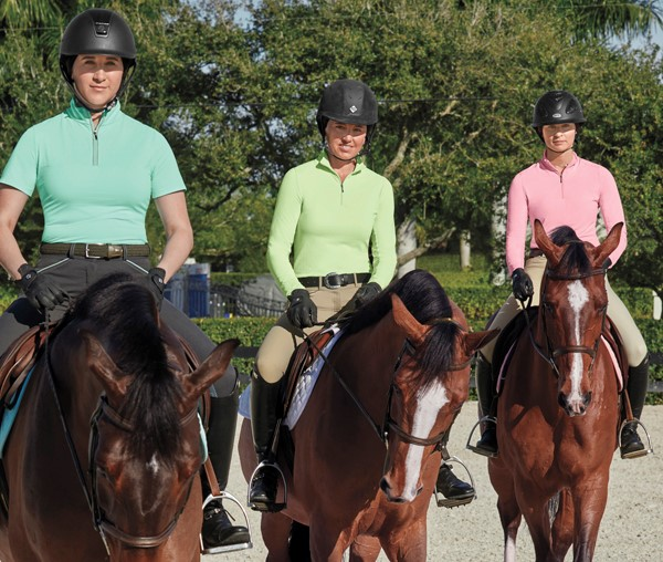 Three riders are on their horses wearing sun shirts to protect themselves from the sun while they ride.